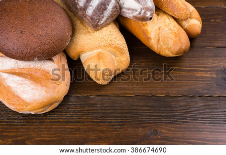 Close up of ends of whole french bread and rye loaves topped with flour over dark wooden table - stock photo