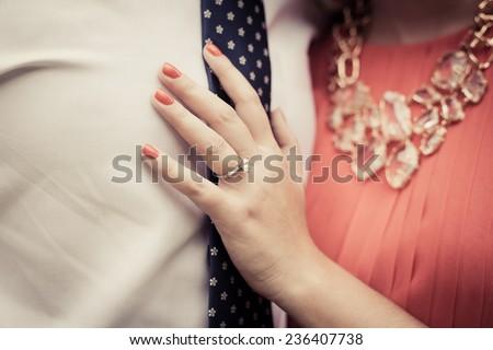 Close up of engaged couple showing diamond ring  - stock photo