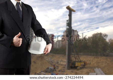 Close up of engineer hand holding white safety helmet for workers security, giving thumbs up success sign, standing in front of  blurred construction site in background - stock photo