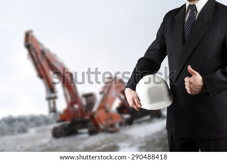 Close up of engineer hand holding white safety helmet for workers security standing in front of  blurred construction site with cranes in background - stock photo