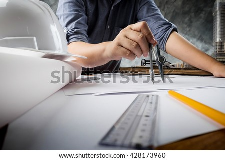 Close up of engineer hand sketching a construction project with Pencil, compass. Business meeting concept. - stock photo