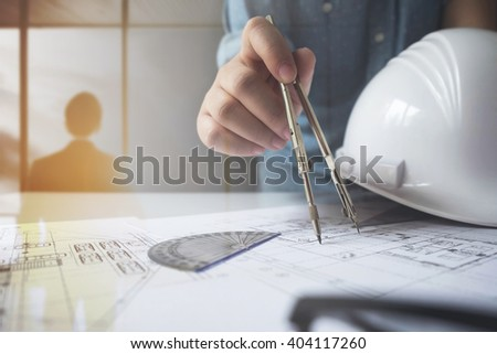 Close up of engineer hand sketching a construction project with Pencil, compass. Double exposure with business man standing at workplace. - stock photo