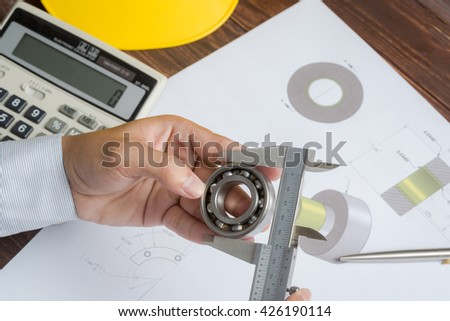 Close up of engineer to measuring outside diameter of bearing by vernier caliper
