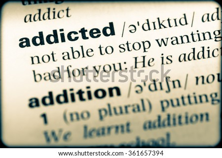 Close up of English dictionary page with word addicted - stock photo