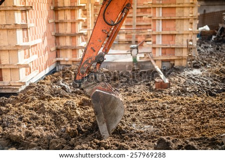 Close up of excavator scoop digging earth at construction site - stock photo