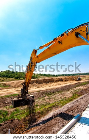 Close-up of excavator while working in road and highway construction site - stock photo