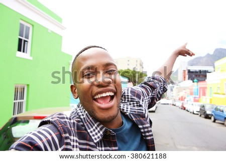 Close up of excited young african guy out on the city street taking a self portrait - stock photo