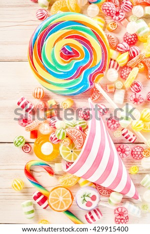 Close up of extra large swirly colored sucker besides confections wrapped in stripped paper and fruit flavored gummy candy