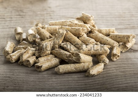Close up of extruded wood pellets on wooden background
