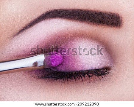 Close up of eye makeup woman applying eyeshadow powder - stock photo