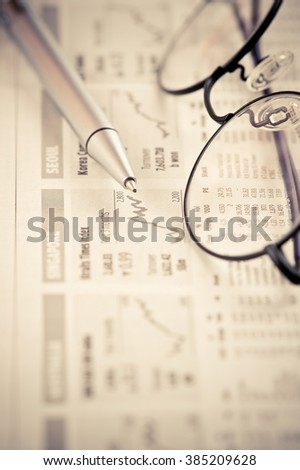 Close-up of eyeglasses and ballpoint pen over graph chart. - stock photo