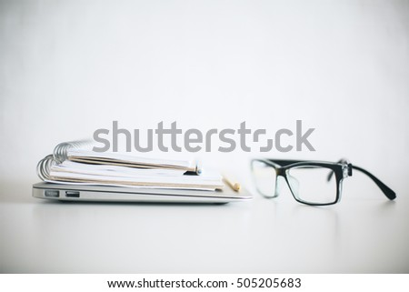 Close up of eyeglasses, closed laptop and notepads on bright desktop