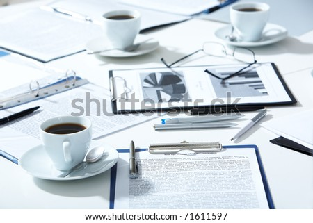 Close-up of eyeglasses, documents, pens, cups of coffee on the table - stock photo