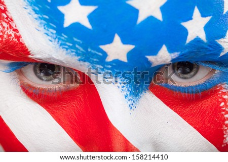 Close up of eyes. Painted face with USA flag looking at camera