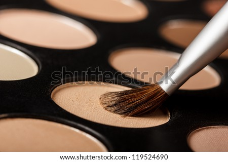 Close-up of eyeshadow palette with brush - stock photo