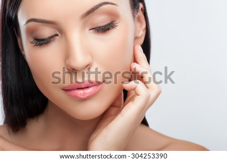 Close up of face of attractive woman touching her cheek gently. She closed her eyes with pleasure. Isolated and copy space in right side - stock photo