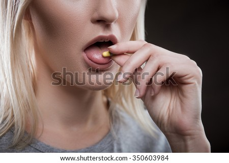 Close up of face of young woman taking drug. The drug addict is standing and putting a pill into her mouth - stock photo