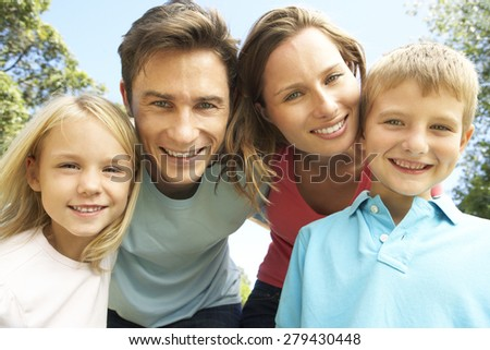 Close Up Of Family Group Looking Into Camera In Park