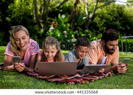 Close-up of family using technologies while lying at yard - stock photo