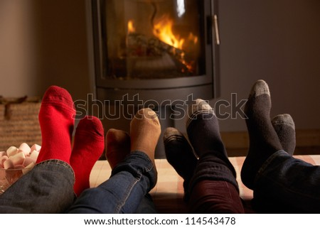 Close Up Of Familys Feet Relaxing By Cosy Log Fire With Marshmallows - stock photo