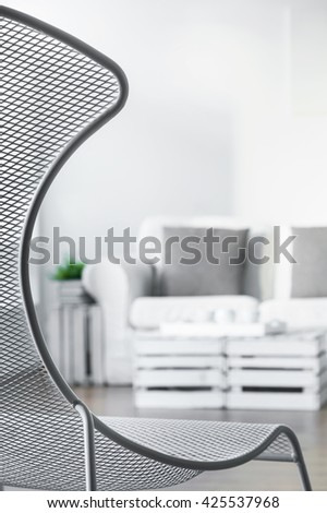 Close-up of fancy armchair in white living room. In the background comfortable sofa with pillows and coffee table - stock photo