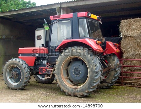 Close up of farm tractor by barn. - stock photo