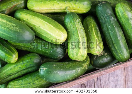Close up of farmers crate with cucumbers on a wooden background.