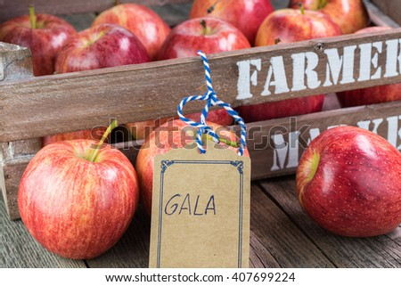 Close up of farmers crate with ripe apples on a wooden background. - stock photo