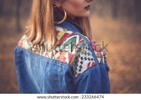 Close up of fashion woman in a romantic autumn fall scenery wearing a denim jacket with geometric print - stock photo