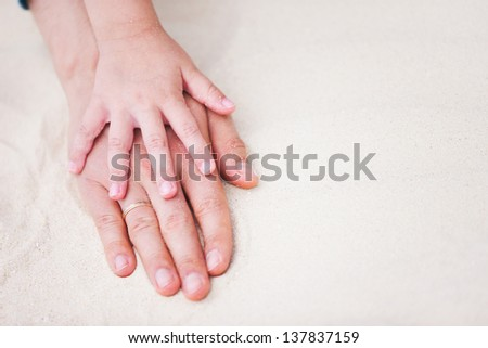 Close up of father and daughter hands on sand