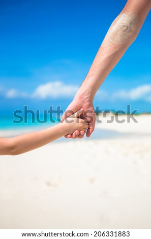 Close up of father and little kid holding each other hands at beach