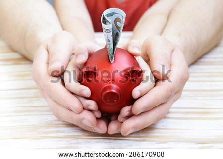 close up of father and son hands holding red piggy bank  - stock photo