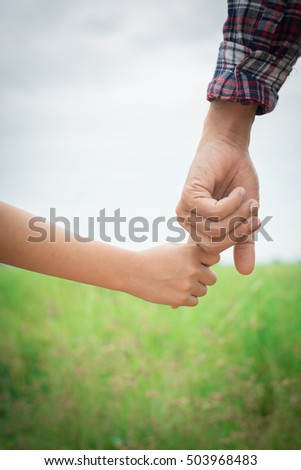 Close up of father holding his daughter hand, so sweet,family time.