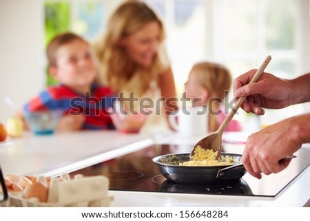 Close Up Of Father Preparing Family Breakfast In Kitchen - stock photo