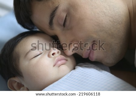 Close up of father sleeping with baby - stock photo