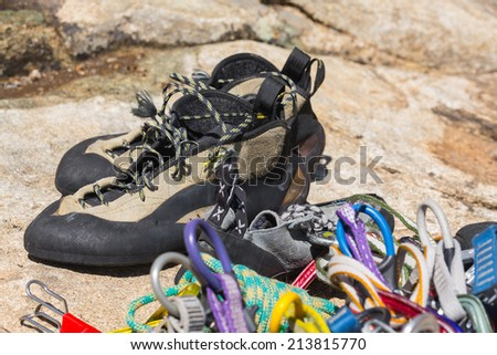 Close up of fawn and black climbing shoes ropes and carabiners on granite rock prior to climb - stock photo