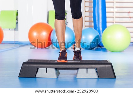 Close up of feet in step equipment at gym. - stock photo