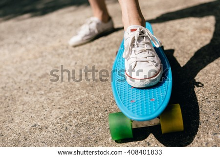Close up of feet of a beautiful woman in white sneakers rides on blue penny skateboard longboard with multicolored wheels. Urban scene, city life. Sport, fitness lifestyle. Cute hipster have fun.