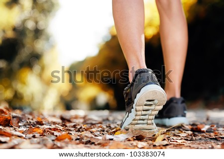 close up of feet of a runner running in autumn leaves training for marathon and fitness healthty lifestyle - stock photo