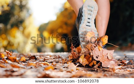 close up of feet of a runner running in autumn leaves training for marathon and fitness healthy lifestyle - stock photo