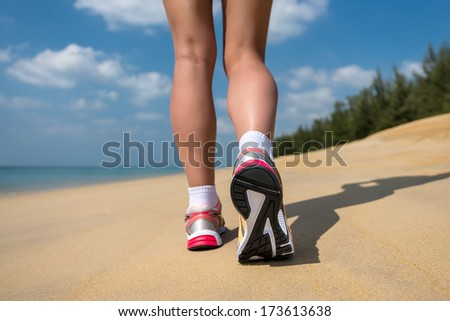 Close up of feet of a runner running in the beach training for marathon and fitness healthy lifestyle wellness concept. - stock photo