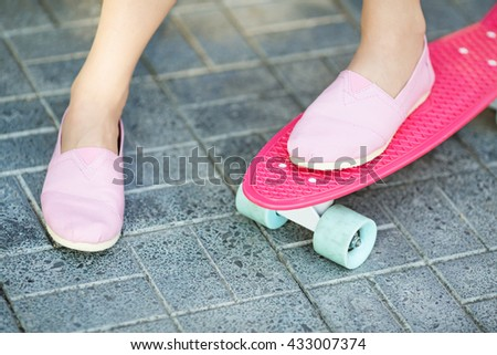 Close up of feet of beautiful girl in pink sneakers rides on pink penny skate board with blue wheels. Urban scene, city life. Sport, fitness lifestyle. Cute hipster have fun. - stock photo