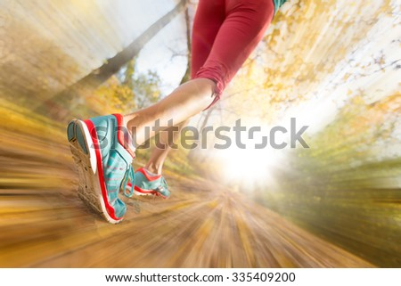 Close up of feet of female runner running in autumn leaves. Fitness exercise. Blur motion - stock photo