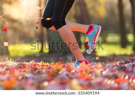 Close up of feet of female runner running in autumn leaves. Fitness exercise, low depth of focus - stock photo