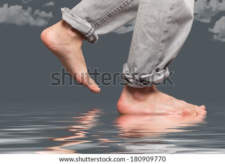 Close up of feet walking by the water  - stock photo