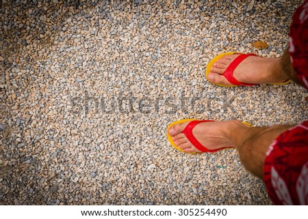 Close up of feet wearing yellow and red flip-flops on the stones
