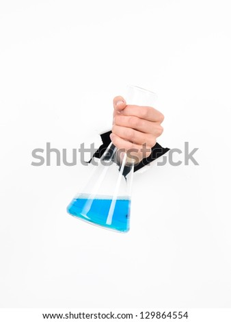 close-up of femal hand holding a chemistry flask with blue liquid in it through a white paper, isolated