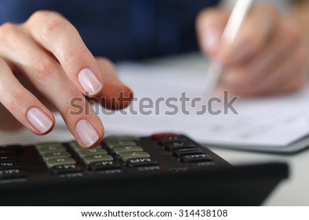 Close up of female accountant or banker making calculations. Savings, finances and economy concept - stock photo