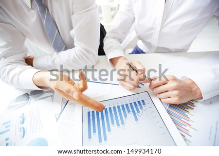 Close-up of female and male hands over business document in touchpad - stock photo
