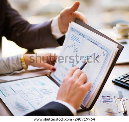 Close-up of female and male hands pointing at business document while discussing it - stock photo